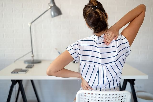 Woman working from home with back pain