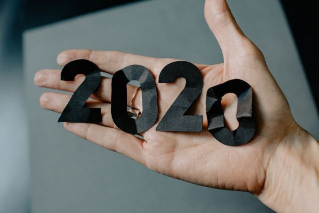 Hand with paper 2020 cut out on top