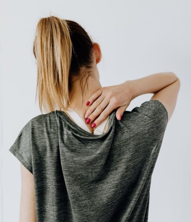 Woman holding her upper back in pain